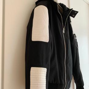 Sort kort jakke med hætte og hvide faux læder stykker. Brugt 5-10 gange, men de hvide stykker har fået mærker (se billeder). Str. L