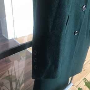 Virkelig fin og meget varm, uld frakke i en lækker mørkegrøn. Jeg har selv været rigtig glad for den, men kan desværre ikke passe den længere - kun gået med en enkelt vinter :)   Meget lille brændmærke forrest og næsten nederst, som du også kan se på billederne. udover det, er den i helt fin stand og fortjener helt sikkert en ny ejer :)