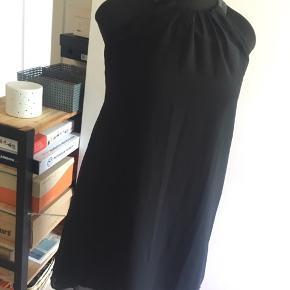 Smuk kjoletop i sort chiffon m. tyndt inderfor og flot detalje med stropper/hals i ægte sort læder. Stropper/hals lukkes med 3 små skjulte hægte i nakken. Går til lige over knæet fortil og til lidt ned på lægmusklen bagerst.  Str. S, som pga. vidden kan passe str. 38-42, dog kun til lille eller medium stor barm, da den ellers kan blive for stram ved armhulerne.   Flot stand, da den kun har været i brug et par gange.  Pris ved afhentning i Nordsjælland ellers + porto.