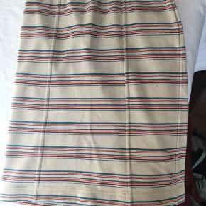 Nederdelen har elastik i taljen og er 60 cm lang