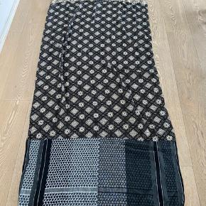 Lækkert stort og langt tørklæde med fine mønstre. Måler 222 x 86 cm. Lavet i 80% polyester og 20% bomuld.