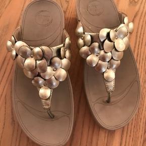 Super flotte bløde FitFlop guld sandal. Nypris 899.-kr Kun brugt få gange. Lille mærke på hø. sandal. Se foto. Sælges meget billigt.
