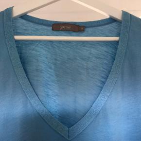 T-shirt i 100% bomuld med glimmer i hals- og ærmekanterne. Prisen er fast