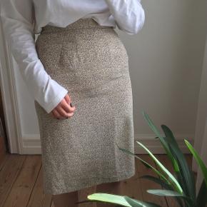 Olivenfarvet nederdel med blomster. Med elastik bagpå i taljen. Passes af en størrelse S/M. I fin stand.
