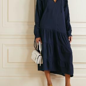 Denne romantiske oversize kjole har et afslappet look, der kan bruges til enhver lejlighed. Kjolen har bindebånd i nakken samt dobbelte bindebånd i ærmekanterne, hvilket giver den et strejf af boheme. Denne flagrende, behagelige og utroligt charmerende kjole vil aldrig gå af mode. Materiale: 100 % bomuld. Mål str. 32: bryst 51cm, længde 131cm. Nypris: 2300kr.