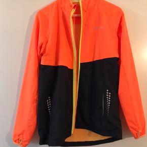 Endurance løbejakke i orange og sort. Jakken har en gul lynlås og lommer i siden. Modellen er en herremodel i str. S men kan sagtens bruges af kvinder også.  Helt ny, aldrig brugt!