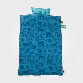 Sebra junior sengetøj med motivet skovens dyr, i blåt - aldrig pakket ud. Er med både pude- og dynebetræk   Størrelse på dynebetræk: 100 x 140 cm. Kvaliteten er: 100% økologisk bomuld.   Værdi: 400 kr. Sælges til 200 kr. - kan afhentes eller sendes med DAO :-)