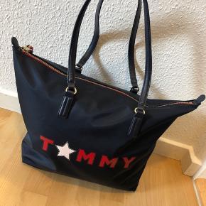 Tommy Hilfiger taske Den er købt herinde i samme stand som den er i nu.  Den fejler ikke andet end de små skader i hjørnerene, og kan sagtens stadig bruges.  Afhentes 8000 Aarhus C Sender også med Dao, køber betaler selv fragten.