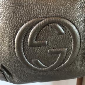 """Meget smuk Guccitaske i gylden metallook. Stor og rummelig.  Den er i tykt, kraftigt læder og har ingen slid eller skader.  Indvendig har den det meget upraktiske lyse og sarte foer. Der er nogle små sorte pletter efter en tusch. Foret er nyrenset og er helt rent trods pletterne.   OBS den står KUN som """"god men brugt"""" pga pletterne i foret.   Den er købt i England og mig bekendt har man ikke ku købe denne farve i Dk.   Jeg har desværre mistet kvitt. Men den er naturligvis ægte med serienr.  Jeg ejer og sælger kun ægte vare."""