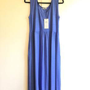 Masai Ona kjole i smuk klar lavendelblå. Farven hedder Blue.  Bærestykke i ribjersey og god vidde i skørtet.  95% viskose, 5% elastan.  Meget rummelig model.   Bryst, uden at strække stoffet: 45 cm, kan nemt strækkes yderligere  20 cm.  Længde: 130 cm  De sidste to fotos viser kjolen i en anden farve, så man kan se modellen på.  Sælger den også i sort og koralrød.   Fra hjem u. tobaksrøg el. dyr.