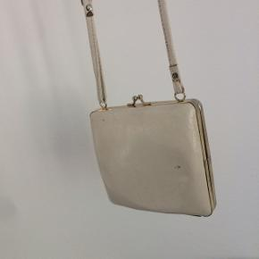 Sød firkantet hvid taske  Justerbar rem. Længste mål 63 fra skuldre og ned til taske