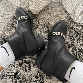 Mega fed støvle med sølv kæde og nitter rundt i kanten. Støvlen er af skind som er meget velholdt. Tegn på slid ved bla lynlås (se billede), men ingen flaws derudover. Jeg er åben for bud