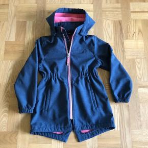 Skøn softshell jakke i mørkeblå med koral farvet fleece for. Str. 122/7 år. Aftagelig hætte. Pæn og velholdt uden slid  og huller.