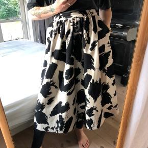 Fin klokkeformet nederdel fra H&M. Den hedder str 38 på mærket, med jeg har haft den syet ind til str 36 i taljen. Den har lynlås, knapper og to lommer.  Smukke malestrøg mønster i creme og sort farve.