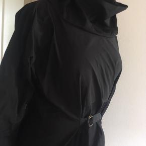 """Hscph/The X Collection fra designeren Henriette Steffensen.   Smuk sort rå kjole i strukturvævet kraftigt stof i lækker kvalitet ø.  Flot stor krave, som kan """"stå"""" af sig selv og også bukkes ned. Bånd med spænde fortil, som giver en flot rynkeeffekt på stoffet.  3/4 ærmer med let vidde nedadtil, og de går til mellem albue og håndled.  Str. XL som er let figursyet, hvis båndet spændes ind, men det kan også bæres løsere, som giver mere plads. Den passer bedst en str. 42/44 med medium/lidt stor barm. 100% polyester i blød strukturvævning. Skjult sort lynlås i den ene side, så den er nemmere at få over skuldre, barm og hofter.  Næsten som ny, da den kun er brugt 1 gang til pænt brug.  Pris ved afhentning i Nordsjælland ellers + porto."""