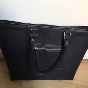 Stor rummelig taske som kan bæres over skulderen eller i håndtagene. Kan lynes lukket. Lille lynlåslomme udenpå, stort inderrum med endnu en lynlåslomme. Aldrig brugt. Fra røgfrit og dyrefrit hjem.
