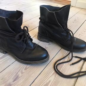 Støvler med lange snørebånd til at binde rundt om støvlen.   Nypris 1100.
