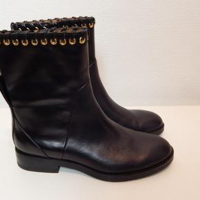 See by Chloé støvler 38½, sort skind med gylden lynlås og ringe, NYE inkl. skopose, er prøvet på, men aldrig brugt! (Købt på Farfetch €410/kr3000) Modellen hedder Black leather Helen Sierra eyelet detail boots