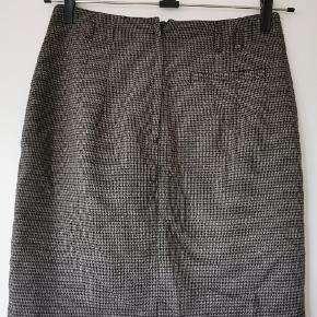 Klassisk pepitta ternet nederdel, med flot knappedetaljer foran. Nederdelen er kort og går til over knæet.
