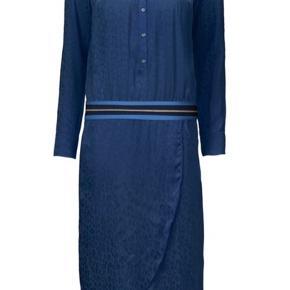 En smuk og elegant kjole fra Gustav i en fin blå farve med et leopard print. Kjolen har diskret knapgang ned langs fronten og lange ærmer med manchet. Der er et bredt elastikbånd i glimmer i taljen og gode lommer. Skørtet har et asymmetrisk snit. Helt ny og med mærke på endnu