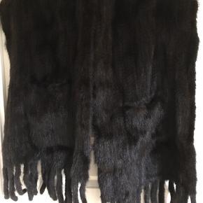 Fint strikket mink halstørklæde, meget mørkebrunt næsten sort, 175 cm uden frynser, 200 cm med frynser, 50 cm bredt, lommer i begge ender. 7-8 gammelt fået i gave, kun brugt 1 gang, passer ikke til mig
