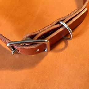 Håndlavet kraftigt hundehalsbånd i Kernelæder.  B 2 cm L efter mål Laves i 4 forskellige læder farver (se billeder) Kraftigt spænde, nitter og ring i metal (sølv)  Få pundslet hundens navn og telefonnummer på gratis.  Halsbåndet får en god gang voks inden det det bliver afhentet/ leveret.