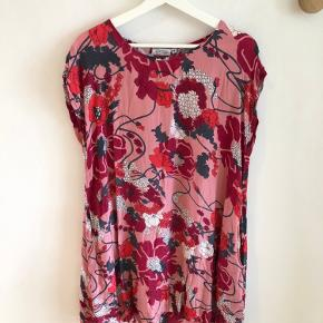Smuk, blomstret kjole i lyserød fra Masai. Er brugt et par gange og fremstår derfor rigtig fin. Kjolen har en lille lomme i den ene side.