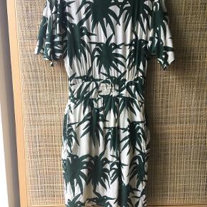 Kjole fra Ganni med palmeprint i modellen Jungle, størrelse xs og med knapper og lynlås bagpå.  Der er elastik i taljen, inderskørt og lommer i siderne. Lette brugstegn i form af lidt vaskefnuller.  Sælger for 400 kr. plus fragt.