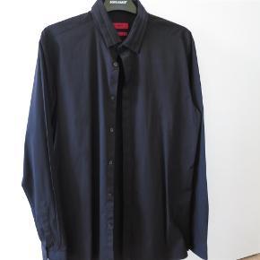 Varetype: herreskjorte Farve: Sort Oprindelig købspris: 1000 kr. Prisen angivet er inklusiv forsendelse.  Skjorte med læg-detalje på kraven, se billeder. Skjorten vil være smart med butterfly til. Modellen er slim og skjorte er kun brugt få gange, derfor ikke forvasket.