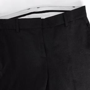 Cool habitbukser i stumpelængde med lommer og smalle ben. Let materiale i Karen BY Simonsens lækre kvalitet. Lommer foran & pyntelommer bag på. Med Bæltestropper. Næsten som ny med pil ned ad. :)  Se også mine andre annoncer og gør en god handel.