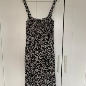 Lækker, let kjole med justerbare stropper sælges. Den er prøvet på og vasket én gang, men aldrig brugt. Den er 3/4 lang, og har smock over brystet.