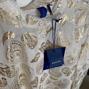 Rigtig fin Resume Tara Skjorte i hvid med gulddetaljer. Skjorte er hvid med et flot print i guld. Skjorten har lange puff-ærmer med balloneffekt og blondedetaljer. Den har kinakrave med blondekant og er gennemknappet med hvide knapper. Så fin og elegant skjorte! Jeg ved godt billedet er af kjolen, men synes printet fortjente at blive vist på, da jeg ikke kan passe skjorten. Den er gået med to timer og er ellers helt ny. Prismærke og silkepapir medfølger.  Respekter venligst at jeg ikke bytter og køber betaler porto samt gebyr ved tspay.