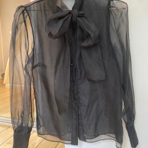 Fin chiffon skjorte med bindebånd i hals til sløjfe. Gennemsigtige ærmer og ryg men fortil mindre gennemsigtig da der er dobbelt stof. Vaskemærket er klippet ud, men har vasket på 30 grader. Har på 2 gange
