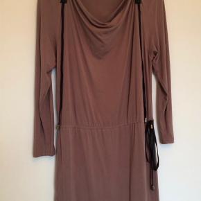 BYD!!!!! Farve: Brun/sort Oprindelig købspris: 700 kr. Super lækker By Groth kjole med imiteret læder indsats, snor i taljen, lange ærmer og vandfald effekt ved udskæringen.  Kvaliteten er 95% viscose og 5% elasthan.  Brugt 1 gang, så fremstår fuldstændig som ny! .