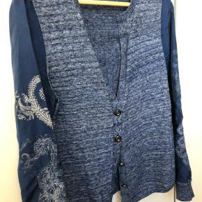 Strik (uld) cardigan med smukke ærmer i 100% silke som både indeholder tryk og broderi. Prisen er fast