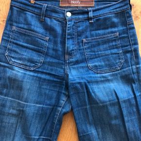 Super fede 70'er jeans/kassebukser fra Notify. Bukserne er kun brugt få gange, men har slid nederst, da de har ramt jorden. Str. 29. Købt i Stig P. Købspris 1800 kr.