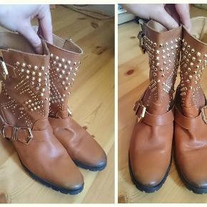 Mega cool biker boots i læder fra ZARA.   De er brugt få gange.   De er lidt mørke omkring snude samt ved hælen, sådan er de købt.  Byd endelig.  Fede Biker støvler med guld nitter Farve: Lysebrun Oprindelig købspris: 900 kr.