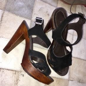 MENTOR str 37 ankelstøvlet sandal med plateau og justerbar ankerlukning, i tykt sort skind. Hæle Højde 11.5cm. Behagelige at have på i god balance.  Fantastisk kvalitet som det forventes af Mentor. Størrelsen er en alm 37.  Foret med skind. Godt rillet undersål så man står fast.  Brugt en enkelt gang - i rigtig pæn NÆSTEN NY stand.   NYPRIS: 1700kr I Magasin  Super lækker ankelstøvle i læder. Den har en rund snude, plateau og hæl af teak træ, og nogle fede detaljer. Denne sko er perfekt til både hverdagsbrug og fest  Mål: Indersål længde: 23.5cm (svært at måle så det er cirka) Højde hæl: 12cm Plateau: 2,5cm