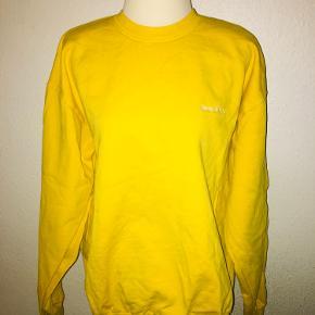 Gul sweatshirt fra sporty & Rich i størrelse large. Vasket en enkelt gang. Med lille Hvidt broderet logo på brystet.
