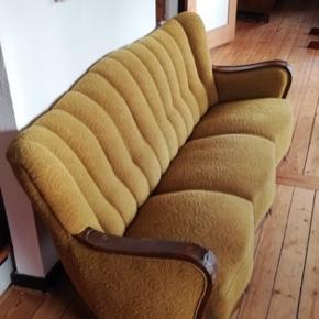 Gul/grøn sofa. Et lille stykke af træet foran er gået af