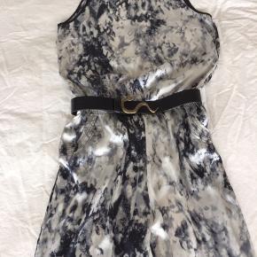 Buksedragt/jumpsuit fra Imitz sælges. Passer en 42/44 - den sidder løst. Smukkeste tie dye farver i blålig/grå/sort. Skjult lynlås i ryggen, 2 lommer med flotte syninger, blonde  m/sten på skuldrene og elastik i taljen. 100% Polyester Kan sendes med DAO for 38 kr  PS. Bælte medfølger ikke