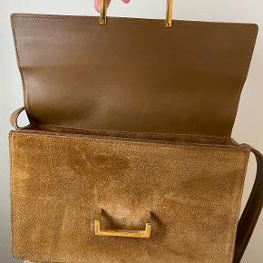 Cross body taske i ruskind fra Saint Laurent der bærer præg af at have været brugt godt, hvilket ses på ruskinden der trænger til en omgang rens eller dampning. Mål: 24x15x6cm Remmen måler 102c´m i yderste hul.