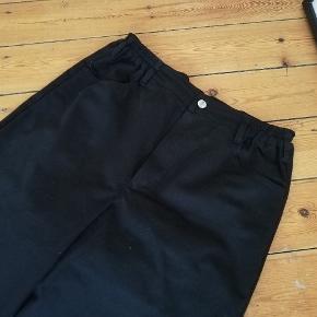 Kentaur work wear højtaljede arbejdsbukser i sort med ekstra lange ben. Materiale minder om Dickies. Passer ca en M/L