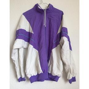 Vintage sportsjakke fra Treat. Hvid og lilla, med turkis kontrast pyntesyning. Lukkes med lynlås foran, og har lommer med lynlås i hver side.   Sender gerne med DAO :)