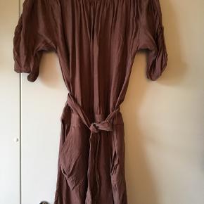 Flot kjole i et virkelig lækkert materiale, som gør at den falder smukt. Farven er noget så fin.   Den ene strop har løsnet sig i siden, og den skal repareres i syningen fortil (se foto)   Passes af en M/L Sendes mod porto.   Nypris: 800 kr Pris: 100 kr.