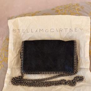 """Stella McCartney Falsbella clutch / crossbody. Den er brugt, men holder sig pænt. Der ses slid på """"siderne"""", hvor at metaller er blevet lidt kobberfarvet visse steder, som ses på sidste billede. Også lidt brugsspor nederst indvendigt. Derfor den gode pris."""