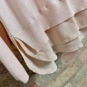 Lang bluse i fint strik, med chiffon detalje nederst, i en lys pudderfarvet rosa.  Længde: 78cm Brystomkreds: 100cm  Sender til GLS eller DAO shop for 38kr.  Prisen er fast, men fri porto ved køb over 300kr, så tjek endelig mine mange andre annoncer...