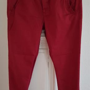 Et par røde chinos fra MOS MOSH, de har sidelommer og en baglomme. Str.: 29 - livvidde 88 cm, skridthøjde foran 30, bagpå 40, indvendig benlængde 75 cm Materiale: 97% Cotton, 3% Elastan Pris: 150 kr. PP