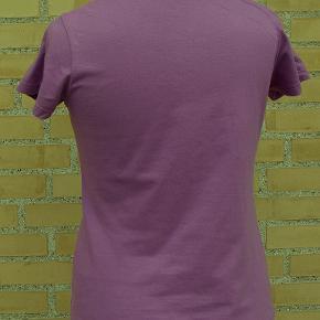 Kortærmet, lyngfarvet bluse med v-hals. Materiale: bomuld.  Str. S, måler ca 90 cm om brystet, ryglængde 58 cm.  Blusen er ubrugt og opbevaret røgfrit.  Sender gerne, men kun som MyPack Collect tracebar pakke med Postnord for 35 kr. (benytter IKKE DAO).