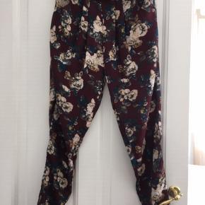 Helt ny blomstrede bukser med løs pasform fra Lollys laundry. har elastik i taljen og sideklommer.  Måler 2 x 64 cm omkring hofterne  Farver: bordeaux, sort, blå, hvid m.m.  Er str xl, 40-42